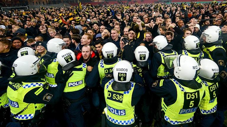 Tusentals fotbollssupportrar som stormar en fotbollsplan.