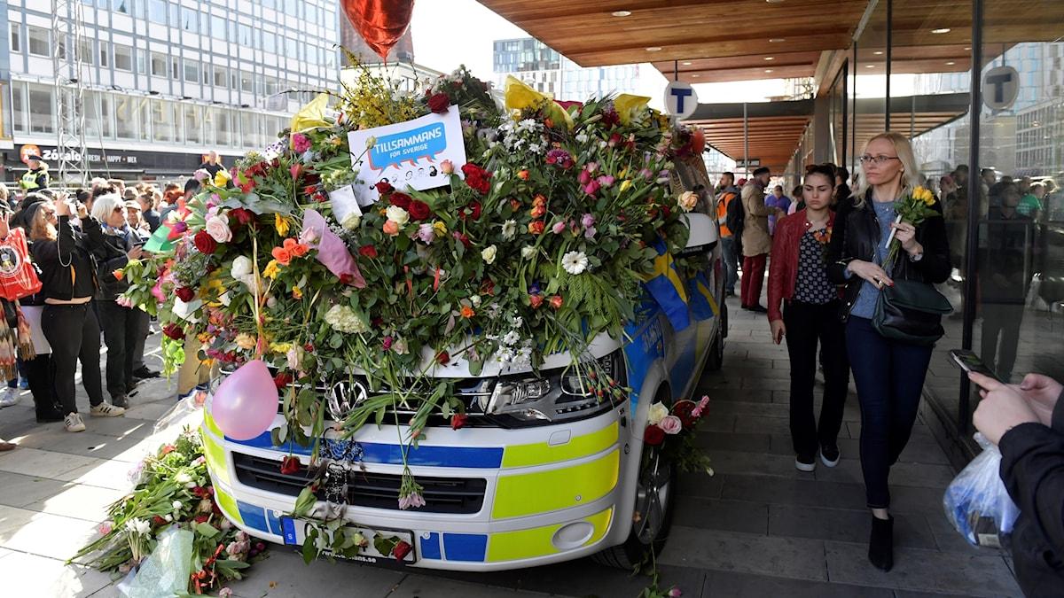 En polisbil täckt av blommor vid Sergels Torg i Stockholm