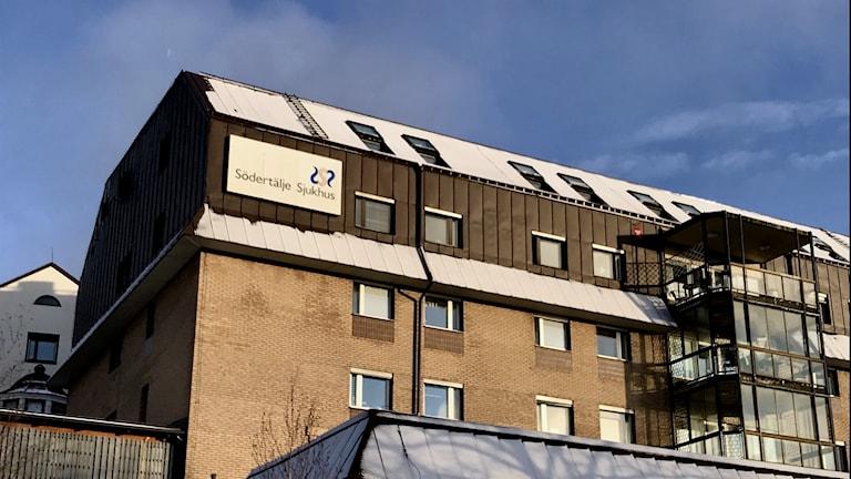 Sjukhusbyggnad med snö på taket.