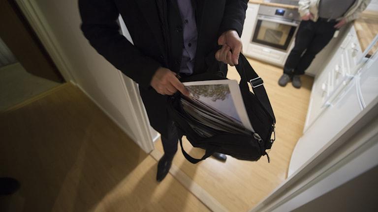 En mäklare stoppar ner en broschyr i sin väska.