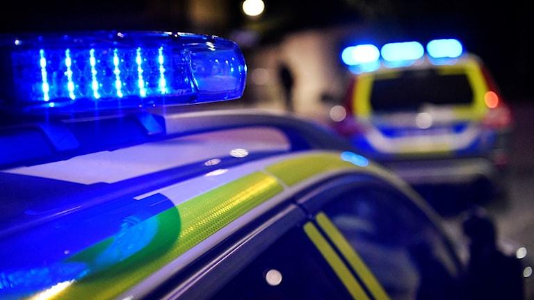 Två polisbilar med blåljusen tända.
