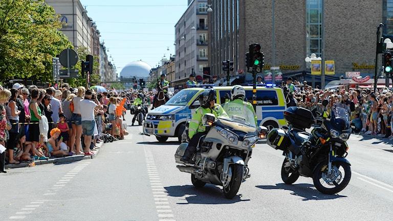 poliser på motorcyklar, till fots och till häst står framför avspärrningar på medborgarplatsen, dit prideparaden är på väg.