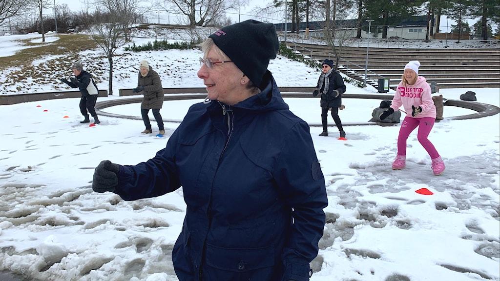 Inger Sahlin, en av deltagarna i Eskilsparken i Haninge utför fyspasset med andra deltagare i bakgrunden.