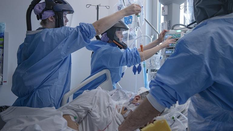Sjukvårdspersonal i skyddskläder tar hand om en patient.