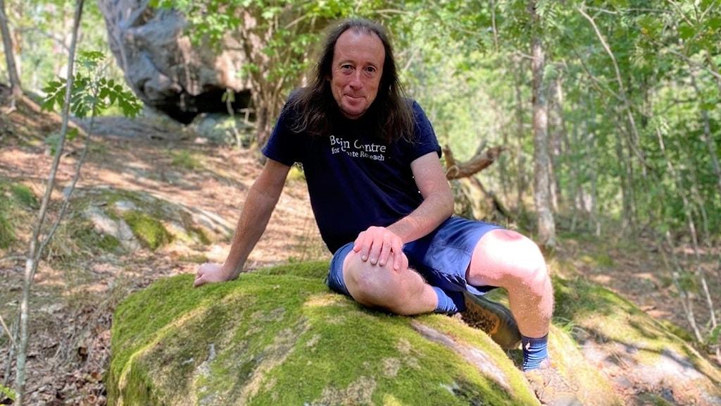 Man sitter på en sten i skogen.