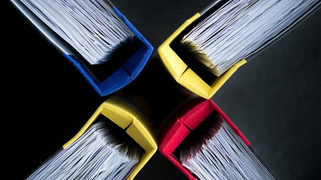 Fyra pärmar fulla med papper, fotograferade uppifrån och ställda med ryggar mot varandra som ett X.