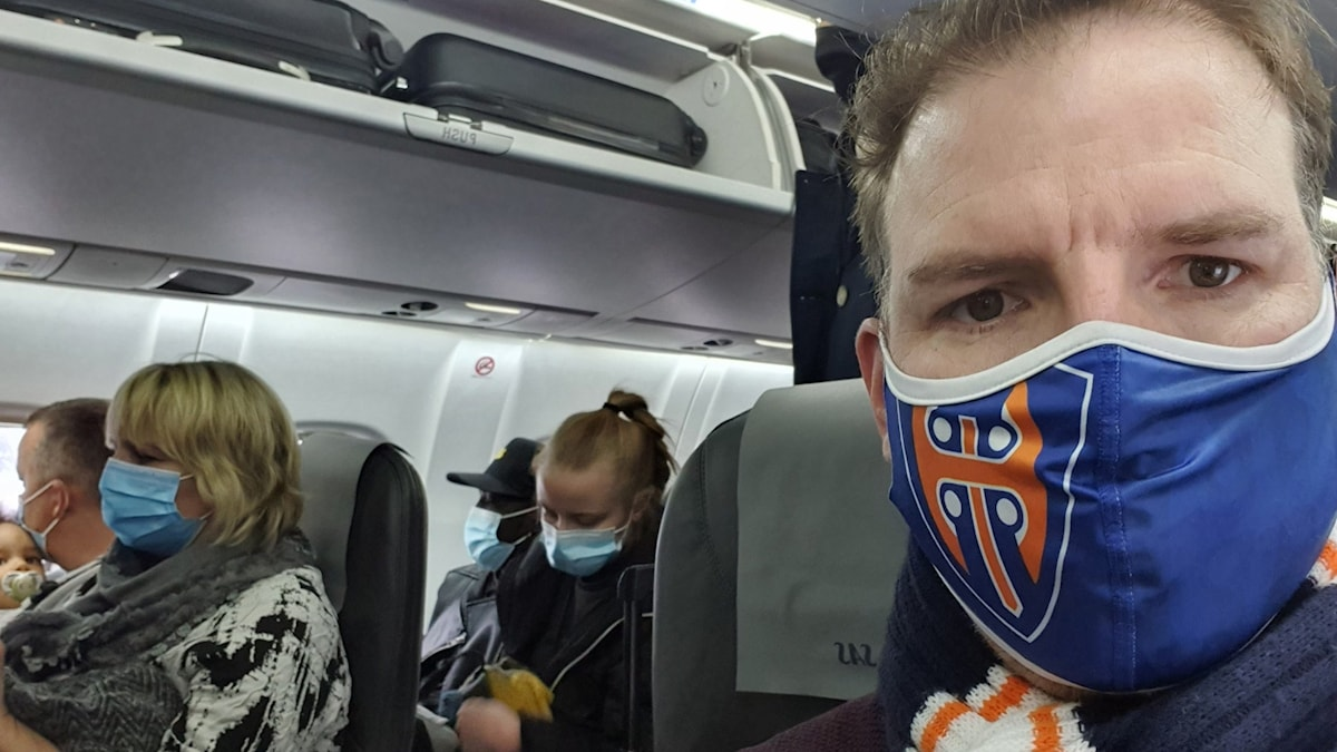 Tobias Minde med blå ansiktsmask på ett fullsatt flygplan.