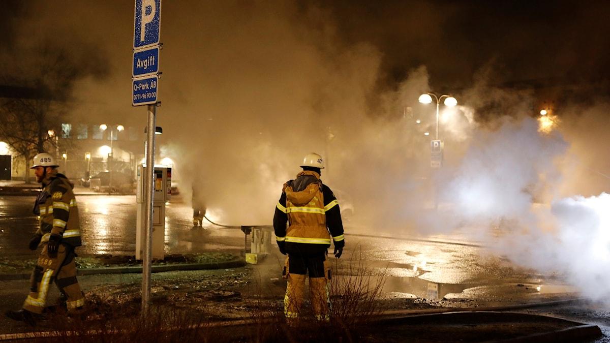 Brandmän vid bilbränder på en parkeringsplats i Rinkeby.