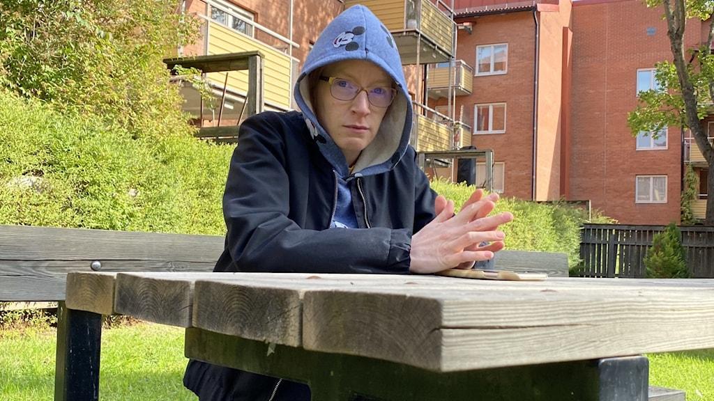 Anna sitter på en bänk utomhus och kollar in i kameran. Hon har luva på sig och ser allvarlig ut. Bakom henne finns grönska och byggnad.