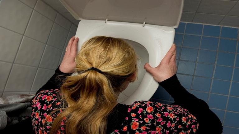 Kräksjuk kvinna med huvudet i toalettstol
