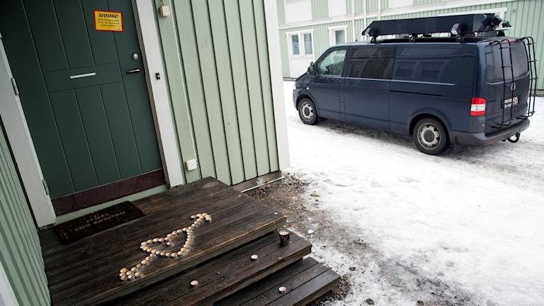 Polisens teknikerbuss och ett hjärta av ljus vid entrén.