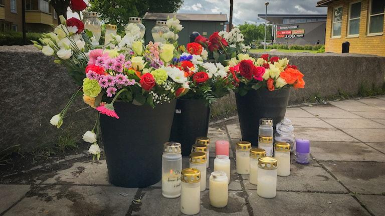 Blommor och ljus vid minnesplats