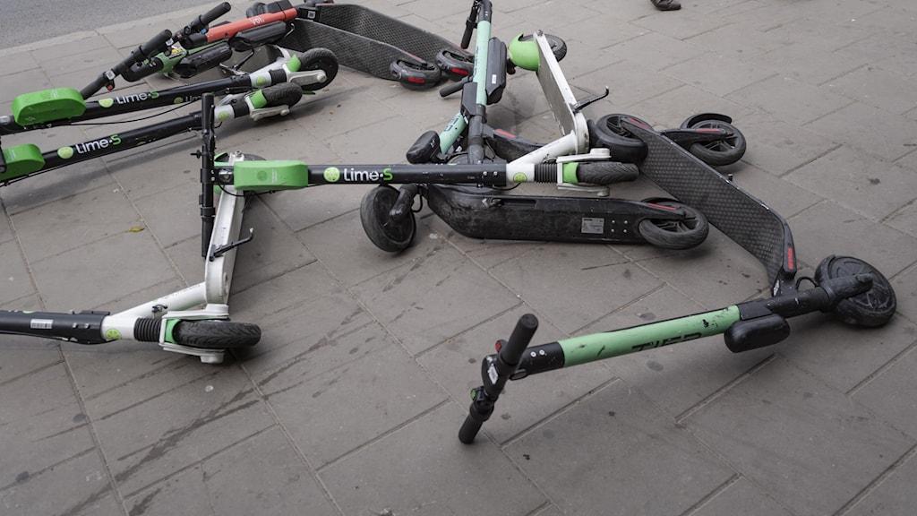 Elsparkcyklar som ligger på marken på Medborgarplatsen i Stockholm.
