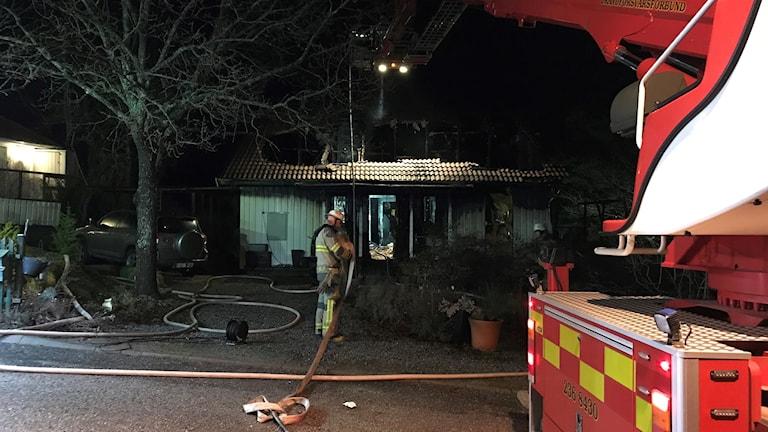 En mer eller mindre totalförstörd enplansvilla i bakgrunden. En brandman med en lång slang är på väg in i huset.