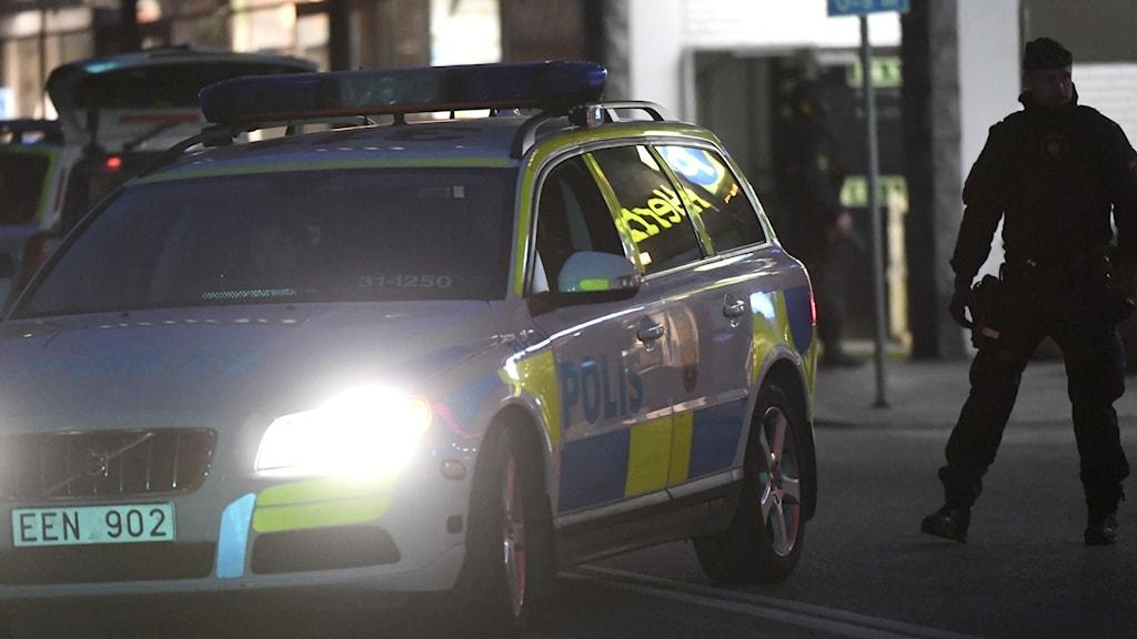 En polisbil och en polisman i mörkret