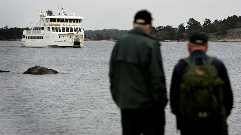 Två män står på en brygga på ön Möja i Stockholms Skärgård och väntar på Waxholmsbolagsbåten