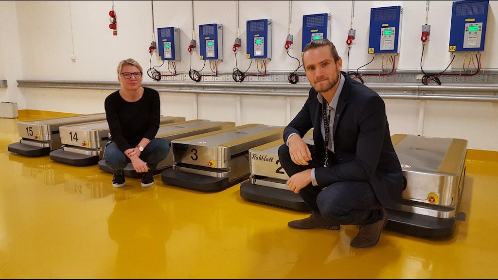 Maria Sonnerby på NSK-PROJEKTET med Nicholas Fernholm som sitter framför robot lådor.