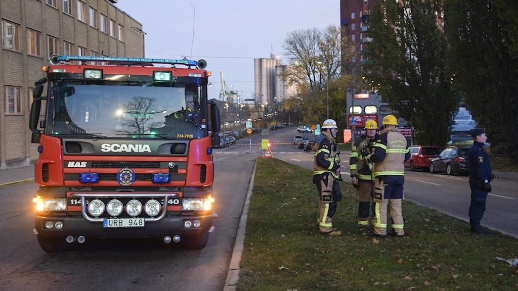 Storstockholms brandförsvar på utryckning, brandmän står utanför fordonet.