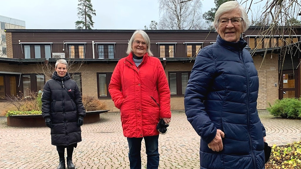 Tre kvinnor utomhus. En i svart, en i röd och en i blå kappa.