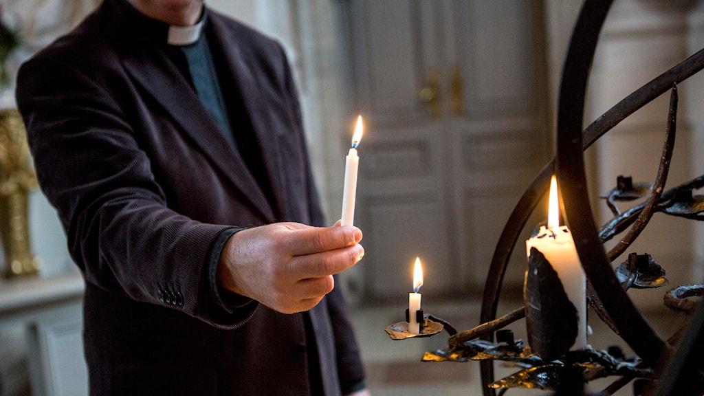 Präst tänder ljus i kyrka.