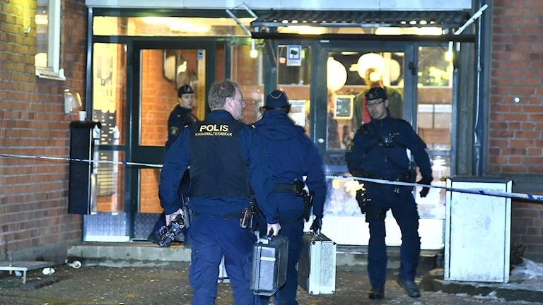 Polisens tekniker på väg in i entrén på Enskede gårds gymnasium.