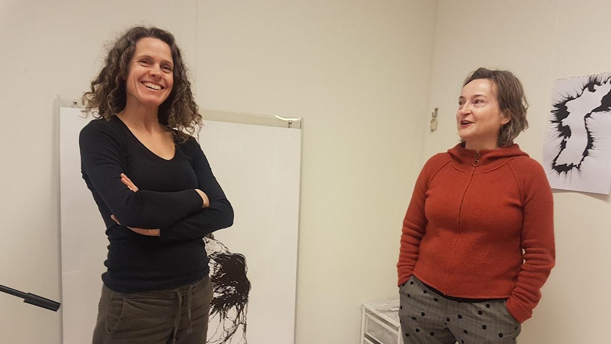 Konstnärerna Johanna Byström Sims och Izabela Knochenhauer står mot en vägg i ateljén i Sundbyberg