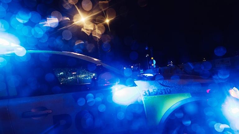 En polisbil med blåljuset igång står på en mörk gata.
