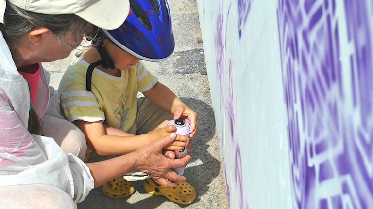 Grafitti Mama opastaa lapsenlastaan spraykannun käytössä Kuva: Iris Honkala/SR