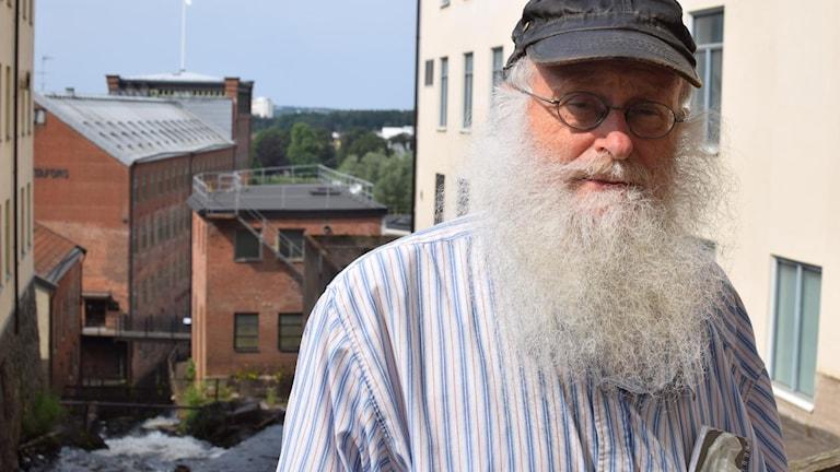 En man med stort och långt vitgrått skägg. Han står utomhus vid Mölndalsån och har en keps på huvudet.