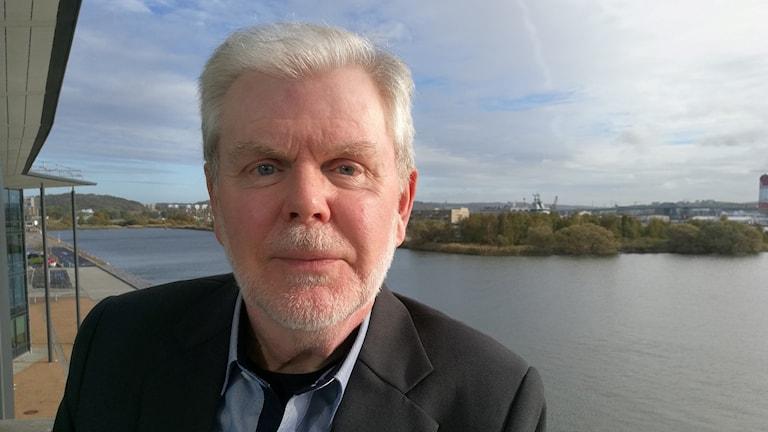 Man med vitt hår och skägg, står i Göteborgs hamn med Götälvbron i bakgrunden.