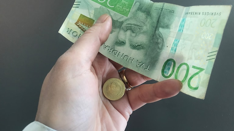 En 200 lapp och en tio kronor i en hand