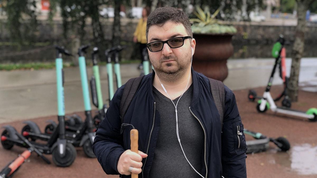 Blind man med käpp i handen och el-sparkcyklar i bakgrunden.