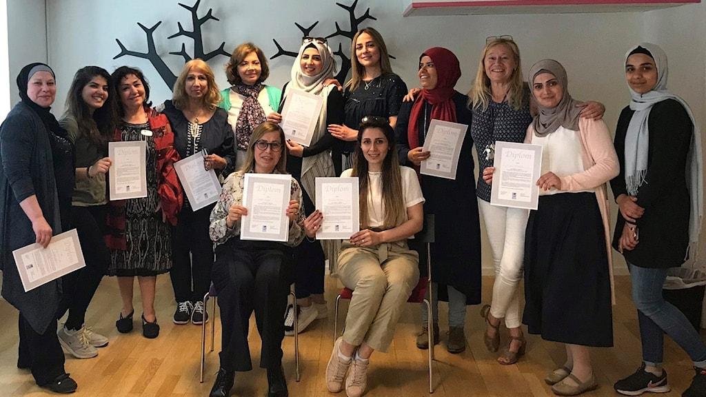 En stor grupp med kvinnor i olika åldrar som håller upp ett diplom.