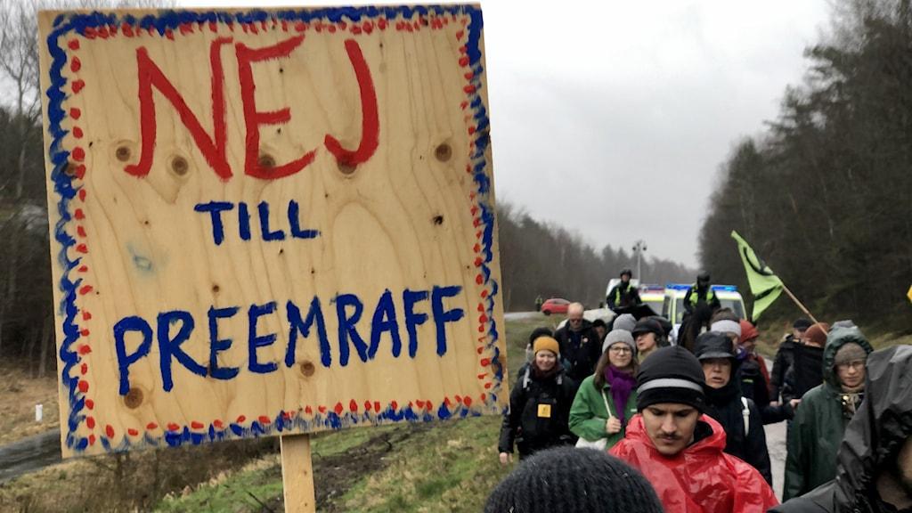 Ett led; en samling klimataktivister marscherar mot Preemraff i Lysekil. De har ockuperat ena vägbanan. Det är en grå, dyster dag.