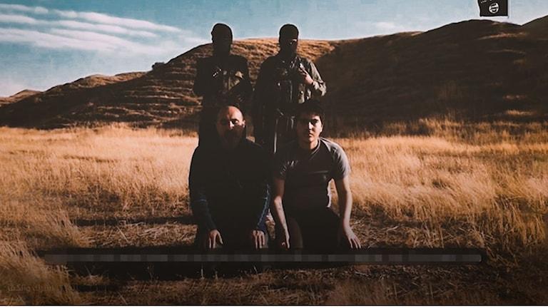 Två män på knä och två maskerade män med vapen står bakom dem ute i en öken.