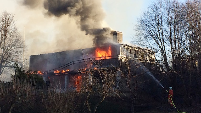 Brandmän sprutar vatten på en brinnande villa.