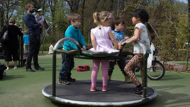 Barn som leker på en snurrande karusell i en lekpark.