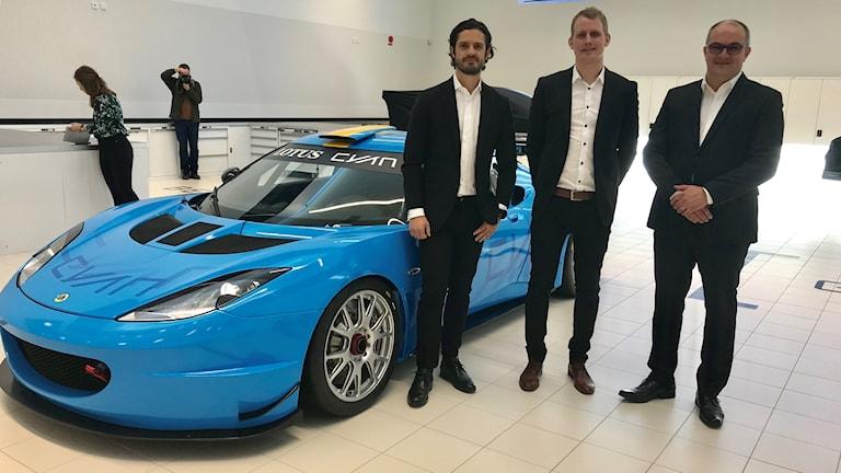 Tre män framför en fin blå racerbil.