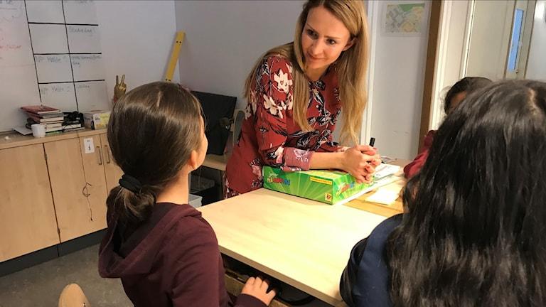 En lärare i ett klassrum tittar på sina elever