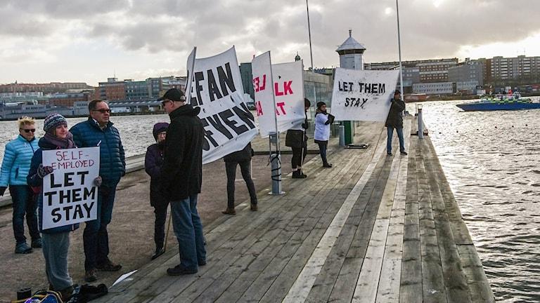 Några personer med plakat och banderoller står på en pir vid Göta älv.