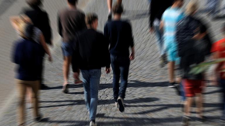Ungdomar går på ett torg, bilden visar personerna bakifrån