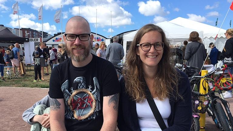 två föräldrar framför en festival