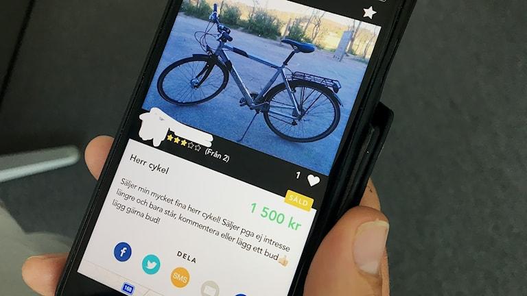 En hand håller en mobiltelefon där cykelannonsen visas på skärmen.