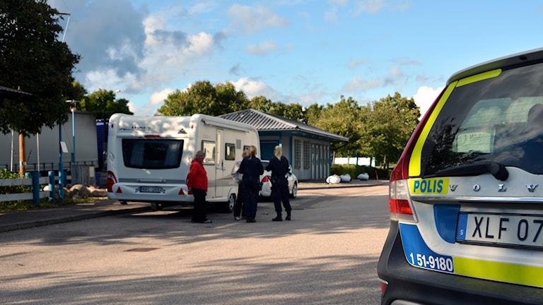 Två poliser samtalar med husvagnsresenärer på en rastplats