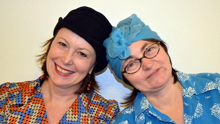 Två kvinnor, i huckle och hatt
