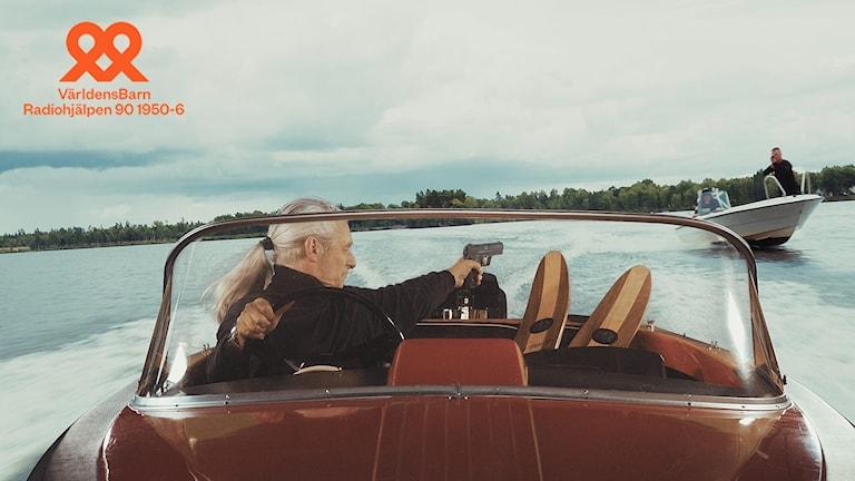 Bild ut filmen: En man med håret i hästsvans kör en liten sportig motorbåt samtidigt som han riktar en pistol mot en mötande båt.