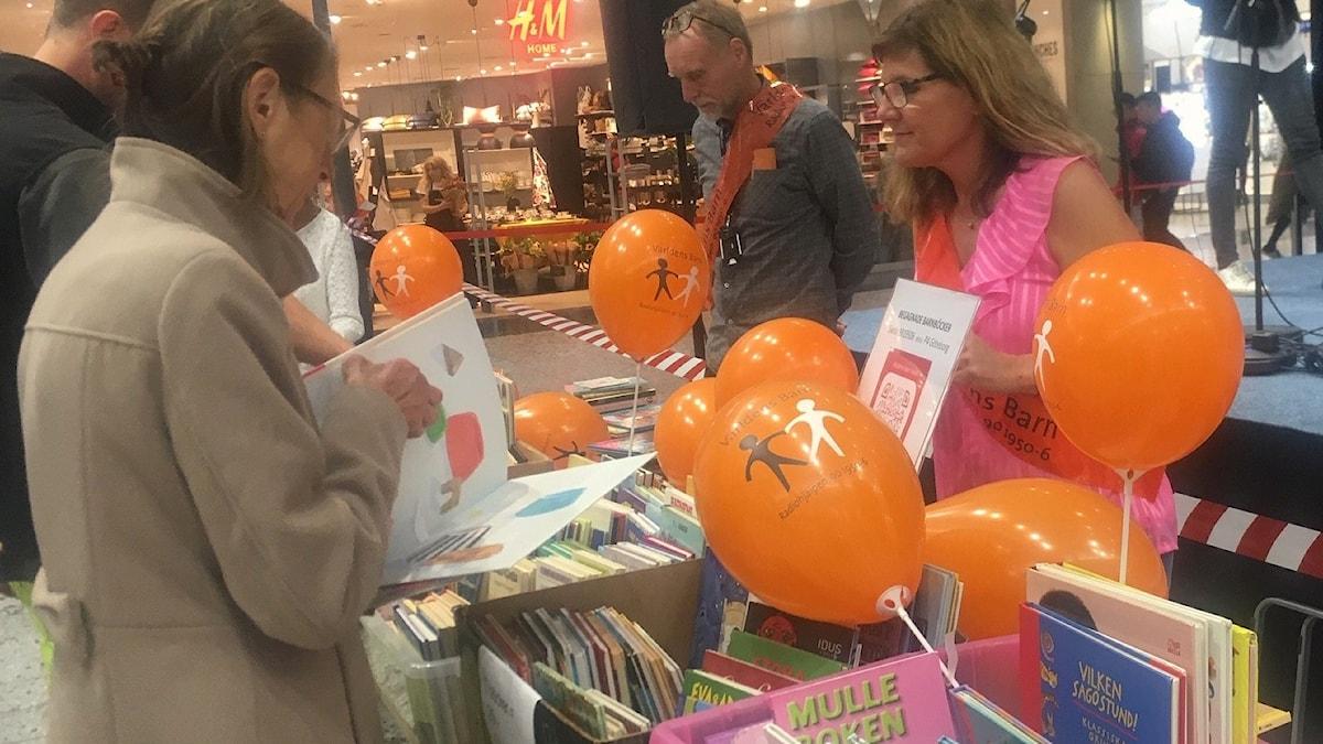 En kvinna står vid ett bord med massor med barnböcker.