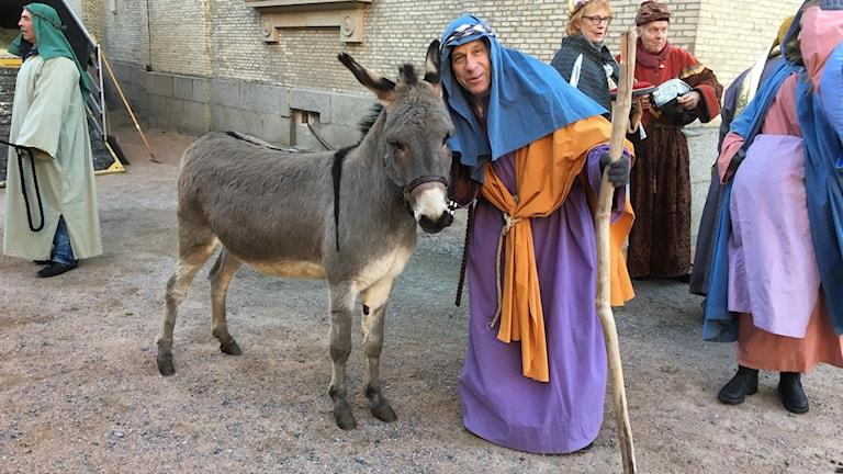 En man med herdeutklädning och en åsna