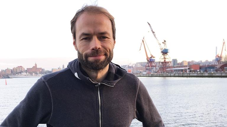 En man med brunt skägg klädd i luvtröja står vid Göta älv.