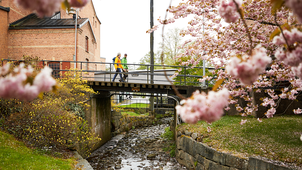 Två personer med ryggsäckar går på en gångbro över en å.